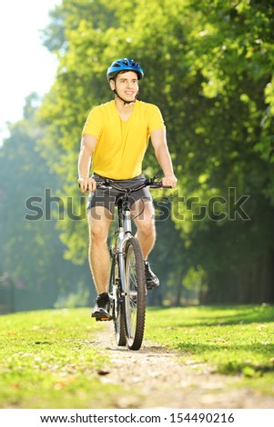 Full length portrait of a young man in yellow shirt biking in a park - stock photo