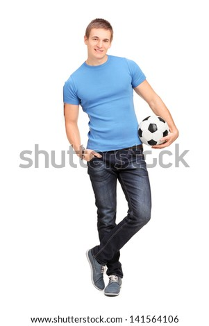 Full length portrait of a young man leaning on a wall and holding a soccer ball isolated on white background - stock photo