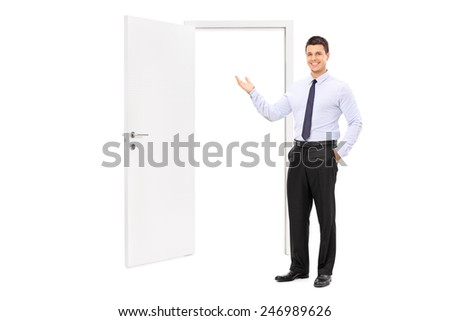 Full length portrait of a young man pointing towards an opened door isolated on white background - stock photo