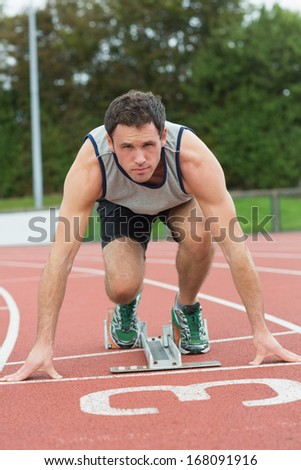 Full length portrait of a young man ready to race on running track - stock photo