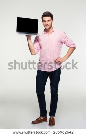 Full length portrait of a young man showing blank laptop screen over gray background and looking at camera - stock photo