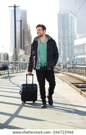 Full length portrait of a young man smiling with suitcase on train station platform - stock photo