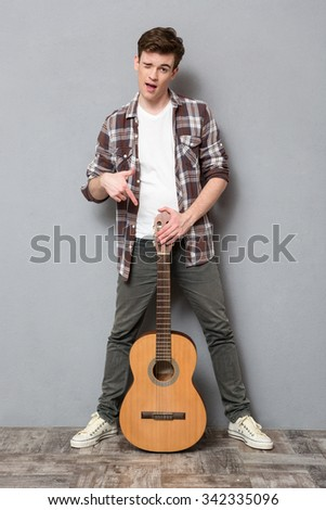 Full length portrait of a young man winking and pointing finger on guitar on gray background
