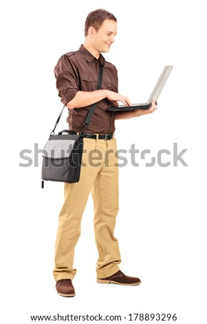 Full length portrait of a young man working on laptop isolated on white background - stock photo