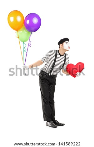 Full length portrait of a young mime artist with balloons and red heart giving kisses isolated on white background - stock photo