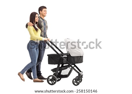 Full length portrait of a young parents pushing a baby stroller isolated on white background