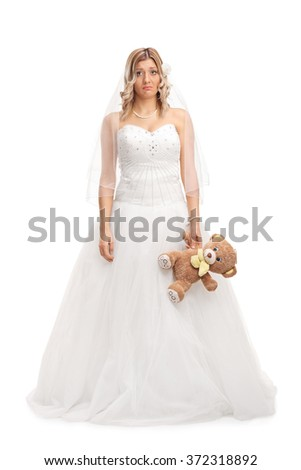 Full length portrait of a young sad bride holding a teddy bear and looking at the camera isolated on white background - stock photo