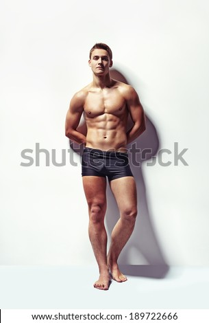Full length portrait of a young sexy muscular man in underwear against white wall - stock photo