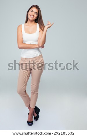 Full length portrait of a young smiling woman standing over gray background. Looking at camera - stock photo