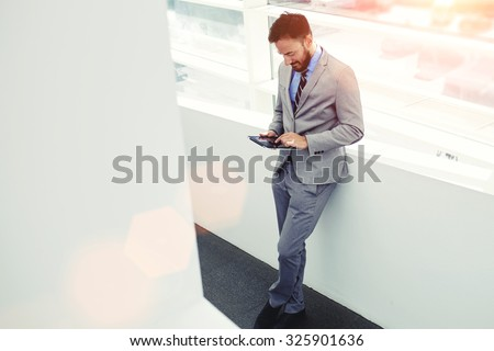 Full length portrait of a young successful man entrepreneur dressed in elegant clothes using touch pad, intelligent male professional worker holding digital tablet while resting after business meeting - stock photo
