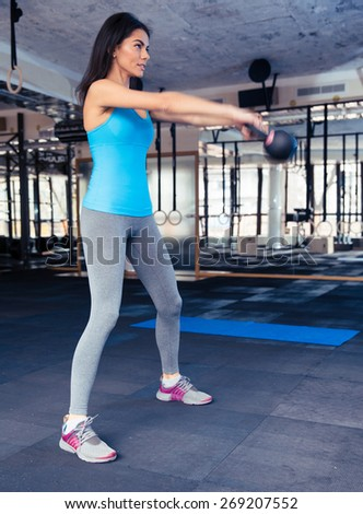 Full length portrait of a young woman attractive young working out at gym - stock photo