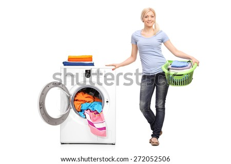 Full length portrait of a young woman holding a laundry basket full of folded clothes and posing next to a washing machine isolated on white background - stock photo