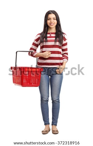 Full length portrait of a young woman holding an empty red shopping basket and looking at the camera isolated on white background