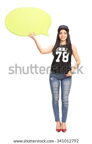 Full length portrait of a young woman in hip-hop clothes holding a yellow speech bubble and looking at the camera isolate on white background - stock photo