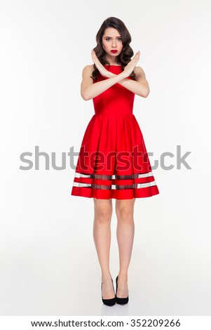 Full length portrait of a young woman in red dress showing stop sign with crossed hands isolated on a white background - stock photo