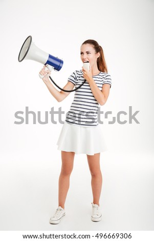 Full length portrait of a young woman shouting in megaphone isolated on a white background