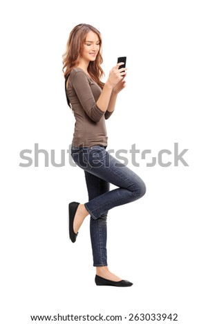 Full length portrait of a young woman typing a text message on her cell phone and leaning against a wall isolated on white background, studio shot - stock photo