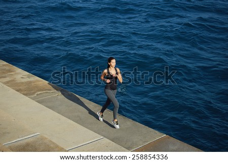Full length portrait of a young woman with fitness body running at the coastline next to the ocean, athletic girl jogging over amazing big waves background at sunny day - stock photo