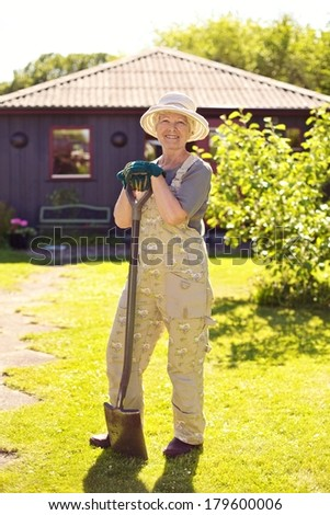 Full length portrait of active senior woman wearing hat with gardening tools smiling outdoors. Elder woman standing with shovel in her backyard garden - stock photo