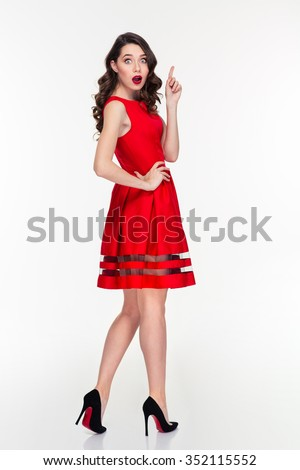 Full length portrait of amazed woman in red dress pointing finger up isolated on a white background - stock photo
