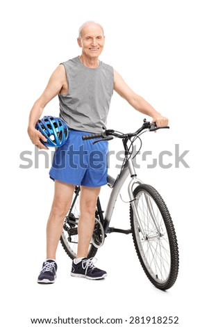 Full length portrait of an active elderly man holding a blue sports helmet and posing next to a bicycle isolated on white background - stock photo