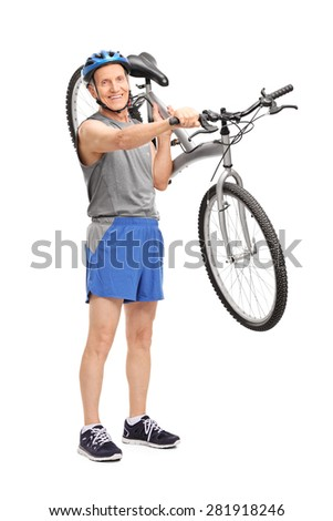 Full length portrait of an active senior biker carrying his bicycle over his shoulder and looking at the camera isolated on white background - stock photo