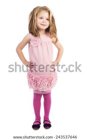 Full length portrait of an adorable little girl holding hands on hips over white background - stock photo