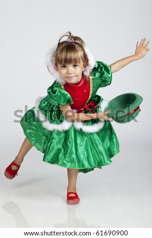 Full length portrait of an adorable little girl wearing green outfit and hat for Saint Patrick's Day, studio image