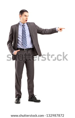 Full length portrait of an angry businessman pointing with his finger, isolated on white background - stock photo