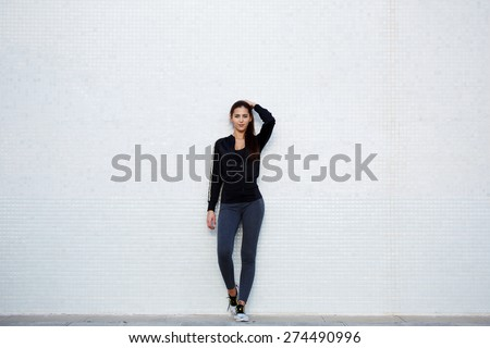 Full length portrait of an attractive and fit young woman standing against a white background while getting ready for workout outdoors, charming girl with fitness body - stock photo