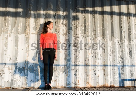 Full length portrait of an attractive brunette hair model dressed in stylish clothing posing on copy space background, young hipster girl with a perfect figure posing against street wall outdoors - stock photo