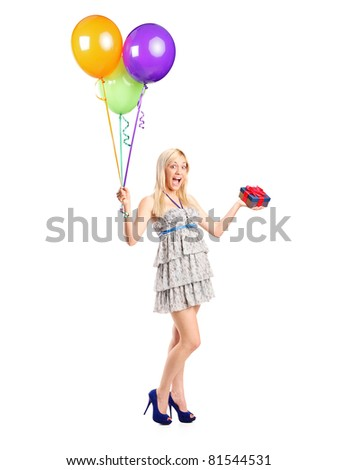 Full length portrait of an attractive woman holding ballons and a gift isolated on white background