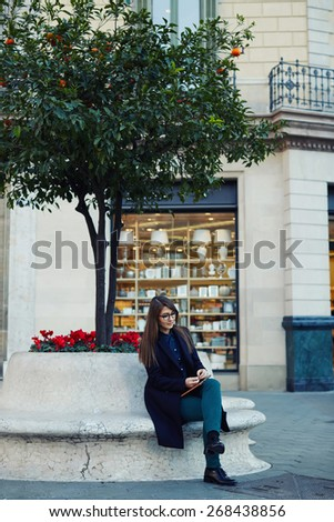 Full length portrait of an attractive young businesswoman sitting outdoors with using her digital tablet for work, elegant university student use digital tablet outdoors, filtered image - stock photo