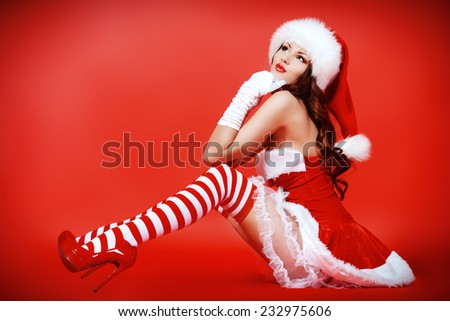 Full length portrait of an attractive young woman in Santa Claus costume over red background. Christmas. - stock photo