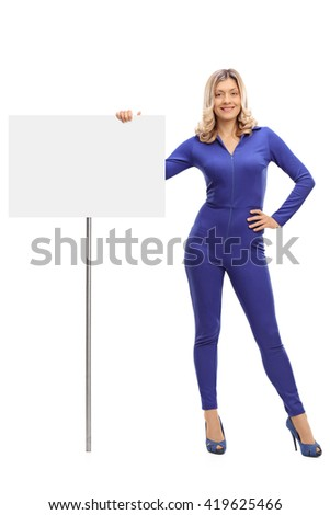 Full length portrait of an attractive young woman standing next to a blank signboard isolated on white background - stock photo