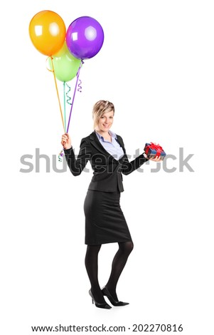 Full length portrait of an elegant woman holding a present and a bunch of balloons isolated on white background - stock photo