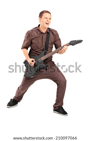 Full length portrait of an energetic young man playing on electric guitar, isolated on white background - stock photo