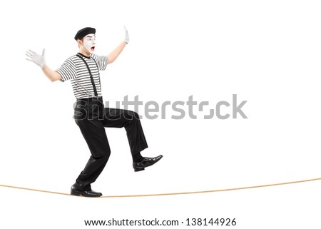 Full length portrait of an excited male mime artist walking on a rope, isolated on white background - stock photo