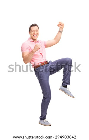 Full length portrait of an excited young guy gesturing happiness and looking at the camera isolated on white background - stock photo