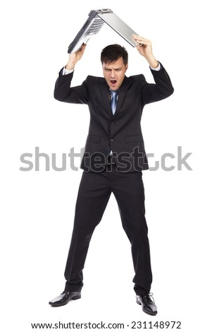 Full length portrait of angry businessman throwing his laptop isolated on white background - stock photo