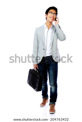 Full length portrait of asian man walking with laptop bag and speaking phone - stock photo