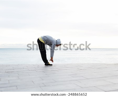 Full length portrait of athletic man doing warm up standing next to the beach before a run - stock photo