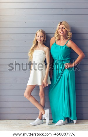 Full length portrait of attractive blondes with blue eyes in dresses, teenage girl and her mother, looking at camera and smiling, standing against gray wall - stock photo