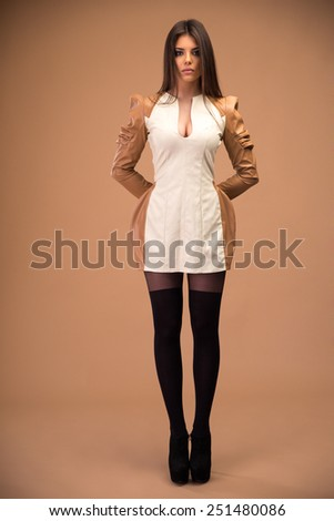 Full length portrait of attractive cute woman standing over brown background - stock photo