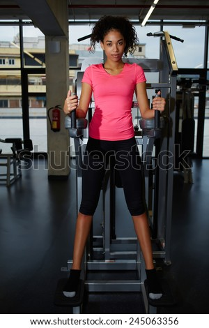Full length portrait of attractive fit woman in pink t-shirt having a rest after workout at gym - stock photo