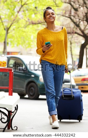 Full length portrait of attractive young african woman walking with suitcase and mobile phone on city street - stock photo