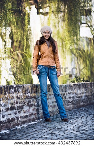 Full Length Portrait of Attractive Young Indian Girl Wearing Leather Jacket and Cap Smiling and Standing with Hands in Pockets on Cobblestone Bridge in Urban Setting with Willow Trees - stock photo