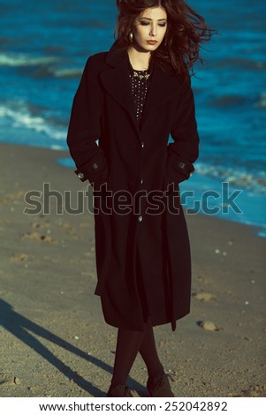 Full length portrait of beautiful brunette with long curly hair in black coat. Luxurious golden accessories: earrings, necklace. Perfect make-up. Street & vogue style. Windy weather. Outdoor shot - stock photo