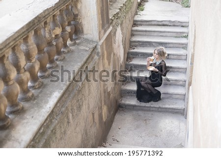 Full length Portrait of Beautiful caucasian woman sitting on concrete old retro abandoned ladder along fence in perspective  - stock photo