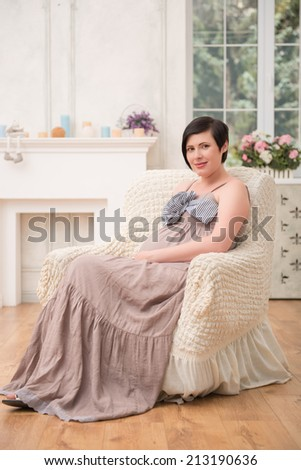 Full-length portrait of beautiful dark-haired smiling pregnant woman wearing great long dress sitting in the very comfortable chair in her living room thinking about her future baby - stock photo